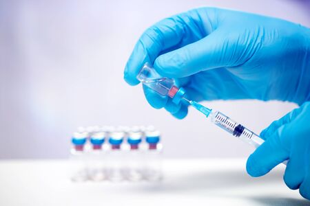 Scientist hand in blue gloves holding coronavirus, covid-19 vaccine disease, preparing for human clinical trials vaccination shot. Medicine and drug concept.