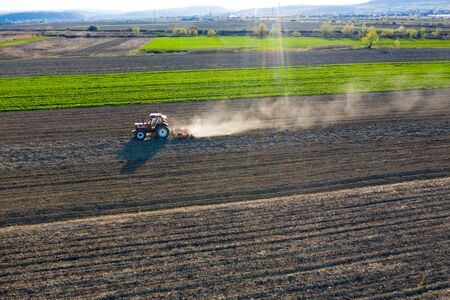 Aerial drone view of tractor working on agriculture spring field. 版權商用圖片