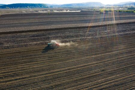 Aerial drone view of tractor working on agriculture spring field.