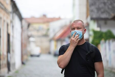 COVID-19 Pandemic Coronavirus. Man in city street wearing face mask protective for spreading of disease virus SARS-CoV-2. Man with protective mask on face against coronavirus disease.