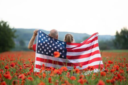 Young couple holding Flag of the United States in beautiful summer field on a clear, sunny day. Celebrating Independence Day, National holiday concept.