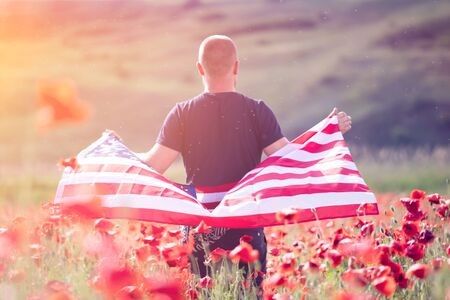 Attractive man holding Flag of the United States in beautiful poppy field on a clear, sunny day. Celebrating Independence Day, National holiday concept.