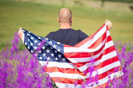 Attractive man holding Flag of the United States in beautiful summer field on a clear, sunny day. Celebrating Independence Day, National holiday concept. Stock Photo