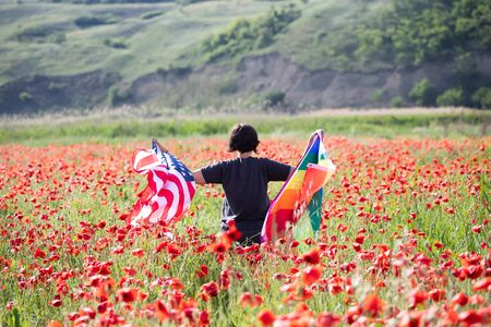 Woman holding LGBT and USA flag in poppy field. Gay equal rights and LGBT freedom in America concept. LGBTQ community advocates for tolerance towards gender, and identity