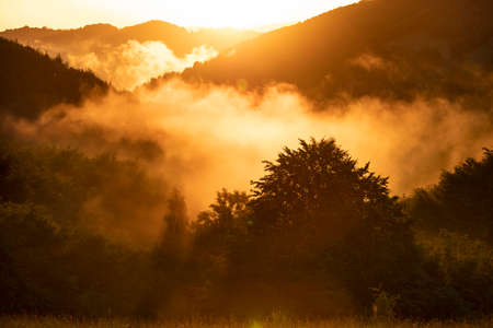 Fantastic dreamy sunset in summer mountains with view into misty valley below.