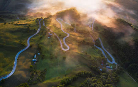 Magic sunrise over foggy countryside valley in transylvanian mountains in the summer - aerial view.