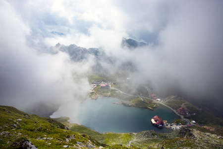 Balea Lake in dramatic foggy weather. Beautiful destination in Fagaras mountain of Romania. View through clouds from the top of a ridge. Banque d'images
