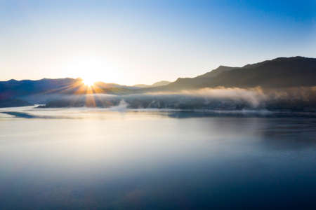 Magic foggy sunrise over Colibita lake at autumn, Romania. 版權商用圖片