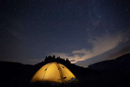 Camping tent glows under a night sky full of stars. Camping, adventure, travel concept.