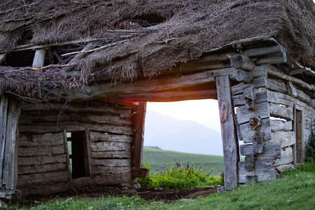Old wooden cottage in summer sunset in Transylvanian mountains.