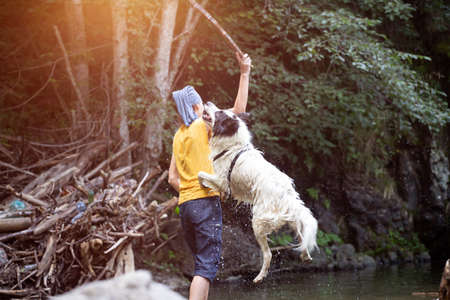 Young woman playing with her dog in the shallow river water in the woods.