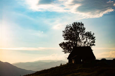 Silhouette of small wooden cottage in Transylvanian mountains agains sunset sky. 版權商用圖片