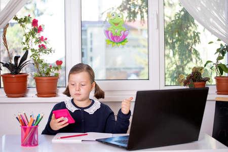 Distance learning-online education. School girl watching online education classes and doing school homework.