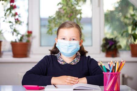 School child wearing mask for protection against virus in school. Standard-Bild
