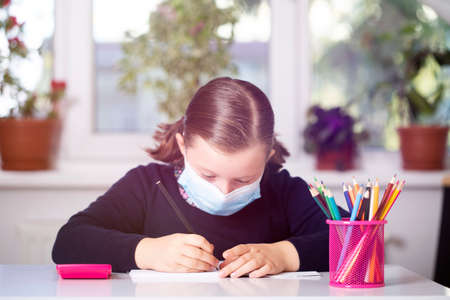 School child wearing mask for protection against virus in school. Measures to prevent the spread of virus pandemic. Standard-Bild