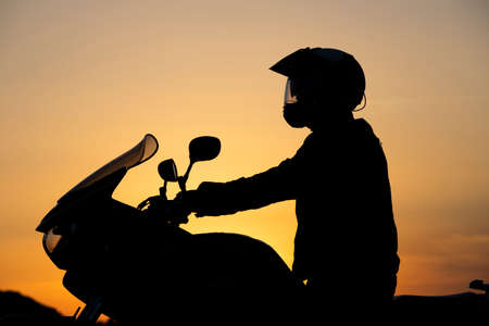 Silhouette of young motorcycle rider on the road with sunset light background. Reklamní fotografie