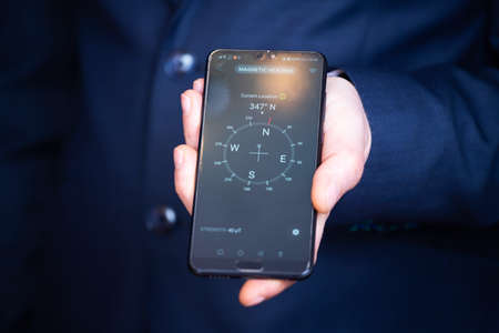 Businessman holding a smartphone with navigation compass. Business planning and strategy growth, progress or success concept