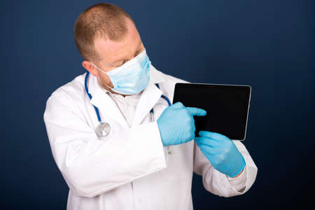 Male doctor using his digital tablet in the consultation.Medicine and healthcare concept