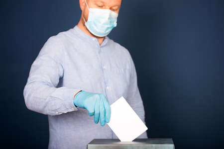 Election in the context of coronavirus pandemic. Person wearing medical mask and protectiv glove placing ballot paper in vote box.