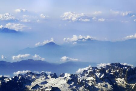snow-caped mountain peaks and clouds in the distance Stock Photo
