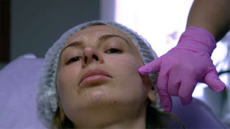 Woman at beautician. Face injections and calming skin mask treatments consultation at beautician. Imagens