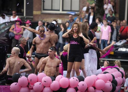 canal parade: AMSTERDAM, THE NETHERLANDS - AUGUST 6, 2011: Visitor at the famous Canal Parade of the Amsterdam Gay Pride 2011 with spectators in the background.