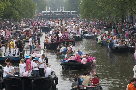 canal parade: AMSTERDAM, THE NETHERLANDS - AUGUST 6, 2011: Crowd on boats in the Amsterdam canals during the famous Canal Parade of the Amsterdam Gay Pride 2011.