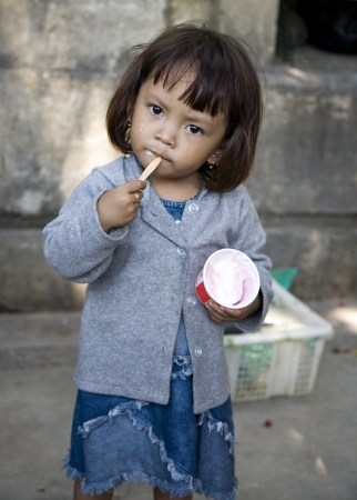 JAKARTA, INDONESIA - AUGUST 2, 2006: Young Indonesian girl enjoys ice cream on the street on August 2, 2006 in Kota Jakarta.