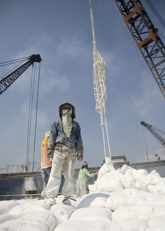 embark: JAKARTA, INDONESIA - JULY 27, 2006: Indonesian port workers unload a ship with a n cement bags cargo in a traditional way in Sunda Kelapa on July 27 in Jakarta, Indonesia