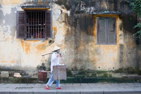 HOI AN, VIETNAM - DECEMBER 14, 2011: Vietnamese seller walking on the streets of Hoi An, 14 december 2011, Hoi An, Vietnam   Stock Photo - 12160090