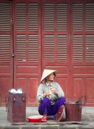 HOI AN, VIETNAM - DECEMBER 17, 2011: Vietnamese seller walking on the streets of Hoi An, 17 december 2011, Hoi An, Vietnam   Editorial
