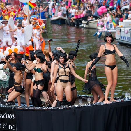 canal parade: AMSTERDAM, THE NETHERLANDS - AUGUST 4, 2012: Participants dance in front of spectators at the famous Canal Parade of the Amsterdam Gay Pride 2012 on August 4, 2012 in Amsterdam