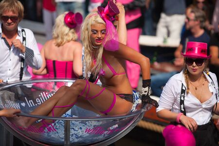 canal parade: AMSTERDAM, THE NETHERLANDS - AUGUST 4, 2012: Woman in lingerie and other participants in front of spectators at the famous Canal Parade of the Amsterdam Gay Pride 2012 on August 4, 2012 in Amsterdam