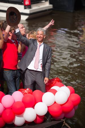 canal parade: AMSTERDAM, THE NETHERLANDS - AUGUST 4, 2012: Politician Ronald Plassterk and other participants dance in front of spectators at the famous Canal Parade of the Amsterdam Gay Pride 2012 on August 4, 2012 in Amsterdam