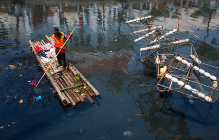 cleaning crew: Jakarta, Indonesia - September 9, 2015: cleaning up a Jakarta canal on a raft in Kota Tua, Jakarta, Indonesia