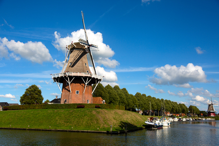 Dokkum, Friesland, The Netherlands - August 17, 2018; Boats on canal and windmill on fortifications of historic town Dokkum, Friesland, The Netherlands 新聞圖片