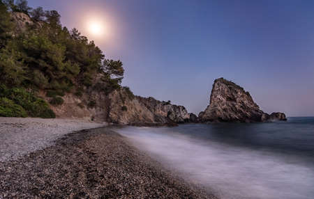 Beach with stones and foam from the waves in the coast, with a cliff and the moon in the background Imagens