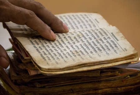 devanagari: A Pujari read old texts from his heap of books and chanted prayers.