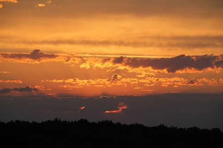 Zonsondergang in de wolken boven een boomgrens Stockfoto