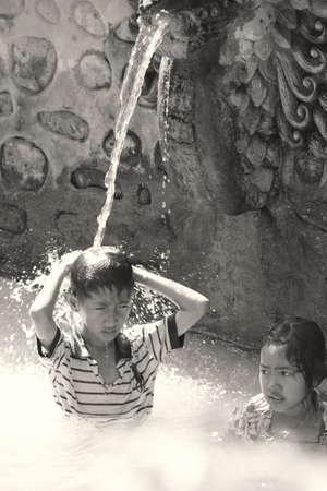 BALI, INDONESIË - juli 2012: Twee niet-geïdentificeerde kinderen baden in de Banjar veren. Volcanous bronnen spuwen 38C warm zwavelhoudend water, die wordt verondersteld om huidziekten te genezen, in 3 grote zwembaden. 10 juli 2012, Bali Indonesië.