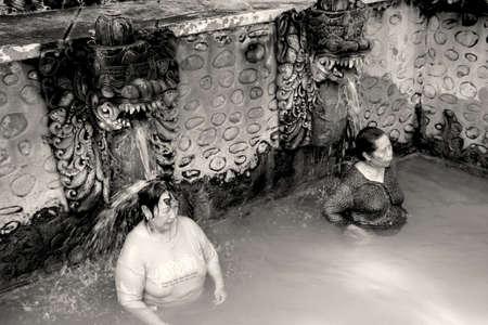 BALI, INDONESIË - juli 2012: Twee niet geïdentificeerde vrouwen worden badend in het Banjar veren. Volcanous bronnen spuwen 38C warm zwavelhoudend water, die wordt verondersteld om huidziekten te genezen, in 3 grote zwembaden. 10 juli 2012, Bali Indonesië.