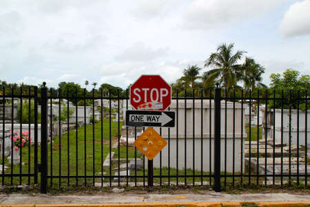 10 key: KEY WEST, FL - AUGUST 2010:  A traffic sign shows the direction alongside the cemetery. One way to the cemetery entrance. August 10, 2010 Key West, Florida.