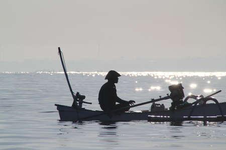 LOVINA, INDON�SIE - juillet 2012: Un p�cheur attend patiemment dans le soleil levant pour les poissons � mordre, avant de se diriger vers le rivage. 10 juillet 2012 � Lovina, Indon�sie