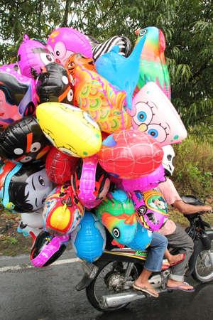 Klungkung, INDONESIË - juli 2012: Een ballon verkoper op weg naar zijn werk, heeft al zijn ballonnen opgeblazen voordat u gaat rijden zijn motorfiets. 13 juli 2012 in de buurt van Klungkung, Indonesië. Editorial