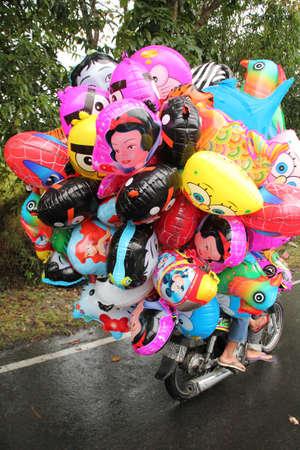 Klungkung, INDONESIË - juli 2012: Een ballon verkoper op weg naar zijn werk, heeft al zijn ballonnen opgeblazen voordat u gaat rijden zijn motorfiets. 13 juli 2012 in de buurt van Klungkung, Indonesië. Redactioneel