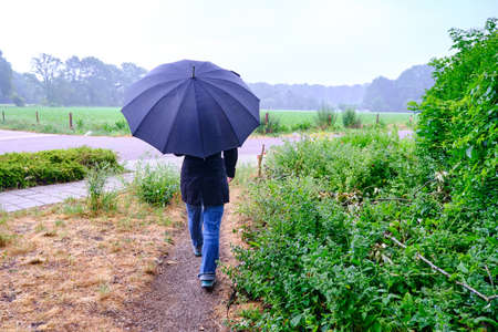 Young woman with umbrella walking in the rain, much needed rain after long drought in the Netherlands