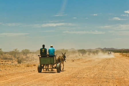 Donkey carriage with 2 men on a dusty dirt road in Namibia, Africa. Driving car with dust cloud in background and blue sky Banque d'images