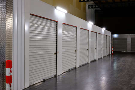 Row of white doors indoor storage units in a self storage facility. Rental Storage Units with red white safety pole. Netherlands Stockfoto