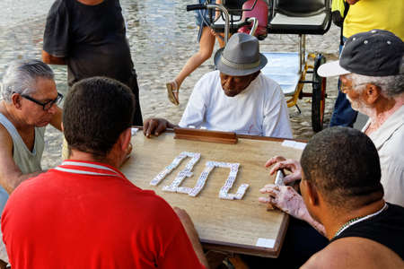 TRINIDAD,CUBA-NOV 23,2013: Five old man on the street of Trinidad playing domino, which is typical game for Cubans who often gather to play it outdoor.