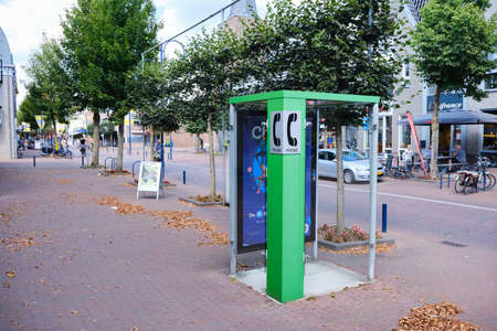Bennekom, Netherlands. Aug,18,2020. Old Green Phone booth in shopping district, one of the last. Green pay phone for general usage, disappear from the streets.